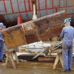 Shipyard volunteers bringing ashore an A-strake plate