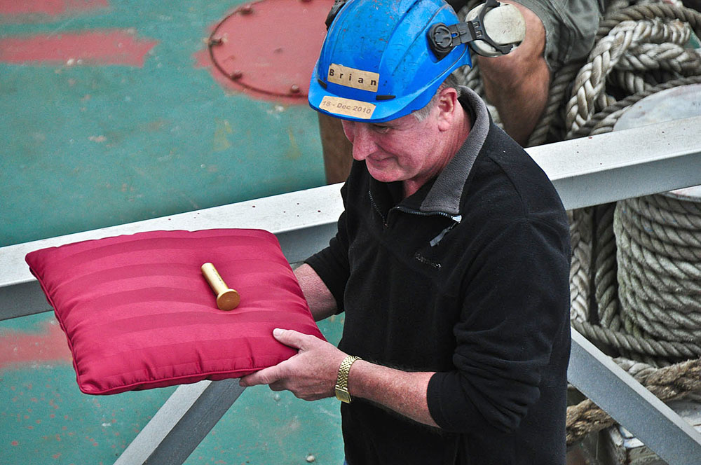 Long term volunteer Brian carries rivet to riveting team